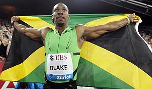 Yohan Blake of Jamaica poses with his country's national flag after winning the men's 100 metres event at the IAAF Diamond League athletics meeting in Zurich on Thursday