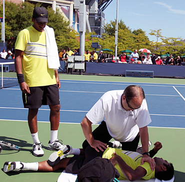 Leander Paes receives medical attention as Mahesh Bhupathi looks on during their doubles match on Thursday