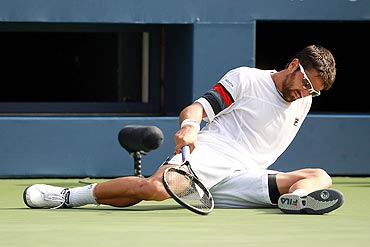 Janko Tipsarevic tries to get up after losing his balance during play against Novak Djokovic