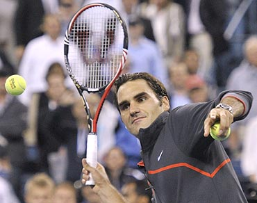 Roger Federer hits autographed balls to fans at the US Open