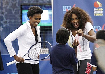 US first lady Michelle Obama and Serena Williams (right) chat with a child as Mrs Obama takes part in a 'Let's Move' tennis clinic at the US Open to promote physical activity for kids, in New York on Friday