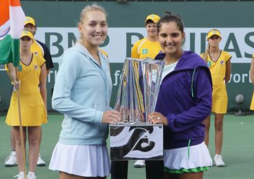 Elena Vesnina (L) and Sania Mirza pose with the trophy after winning the title at Indian Wells in March this year