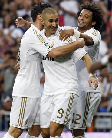 Real Madrid's Karim Benzema (centre) celebrates with teammates Marcelo and Xabi Alonso (left) after scoring against Getafe