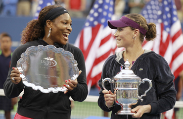 Serena Williams of the U.S. (L) and Samantha Stosur of Australia chat as they hold their trophies after Stosur defeated Williams to win the final of the U.S. Open