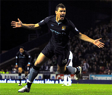 Manchester City's Edin Dzeko celebrates scoring a goal during the English Premier League match