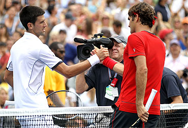 -Roger Federer (R) of Switzerland congratulates Novak Djokovic of Serbia after Djokovic won their match