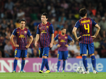 Lionel Messi (2nd L) of FC Barcelona stands dejected with his teammates after conceding a goal during the UEFA Champions League group H match