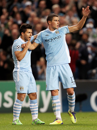 Aleksandar Kolarov of Manchester City celebrates scoring his team's first goal with team mate Sergio Aguero (L) during the UEFA Champions League Group A match