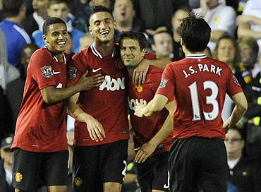 Manchester United's Michael Owen celebrates with teammates after scoring against Leeds United on Tuesday