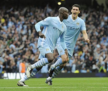 Manchester City's Mario Balotelli (L) celebrates his goal with team mate Gareth Barry during their English Premier League soccer match against Everton at the Etihad Stadium in Manchester