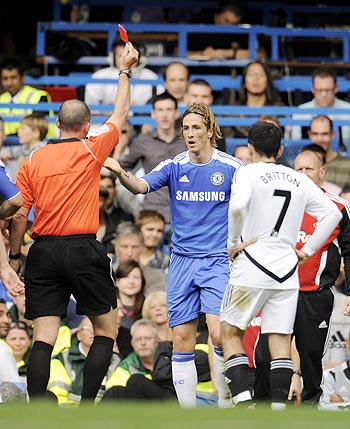 Chelsea's Fernando Torres is shown a red card by referee Mike Dean during the English Premier League soccer match against Swansea City at Stamford bridge