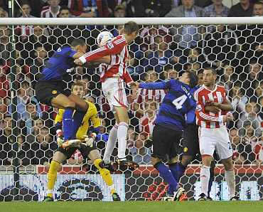 Peter Crouch scores against Manchester United at the Brittanica Stadium