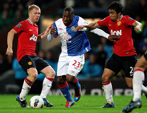 Blackburn Rovers' Junior Hoilett is challenged by Manchester United's Rafael (right) and Paul Scholes