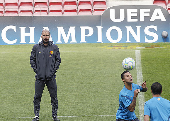 Barcelona's coach Pep Guardiola (left) watches as Tello goes through the grind during a training session at Nou Camp stadium in Barcelona on Monday