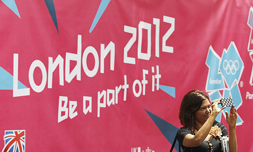 A woman takes a photo in front of a banner showcasing the London 2012 Olympics