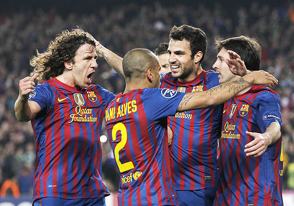 Barcelona's Lionel Messi (right) celebrates with Carles Puyol (left), Daniel Alves (second left) and Cesc Fabregas after scoring a penalty against AC Milan during their Champions League quarter-final second leg soccer match at Camp Nou stadium in Barcelona