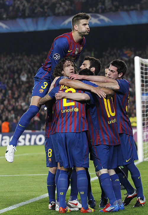 Barcelona's Pique celebrates with team-mates after Messi scored a penalty against AC Milan