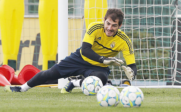 Goalkeeper Iker Casillas of Real Madrid dives for a ball during a training session