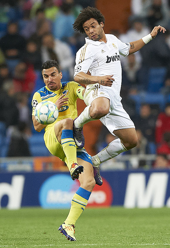 Real Madrid's Marcelo competes for an aerial ball with APOEL's Savvas Poursaitides on Wednesday