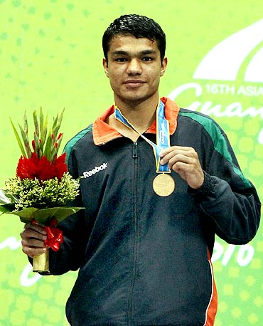 Vikas Krishan Yadav of India holds his gold medal after winning the men's 60kg boxing event at the 16th Asian Games in Guangzhou