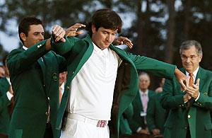 Bubba Watson of the US (centre) receives his green jacket from 2011 champion Charl Schwartzel of South Africa after the 2012 Masters Golf Tournament at the Augusta National Golf Club on Sunday