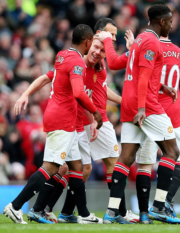 Manchester United players celebrate with Paul Scholes after the veteran midfielder struck the winner against QPR on Sunday