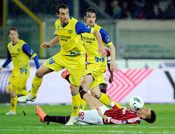 Stepahn El Shaarawy of AC Milan goes down as Dario Dainelli (left) of Chievo Verona vies for the ball during their Serie A match