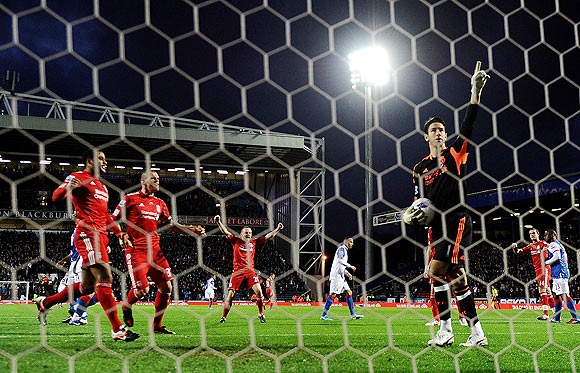 Liverpool 'keeper Brad Jones points to the sky in celebration as he saves the penalty off Yakubu during their match against Blackburn on Tuesday