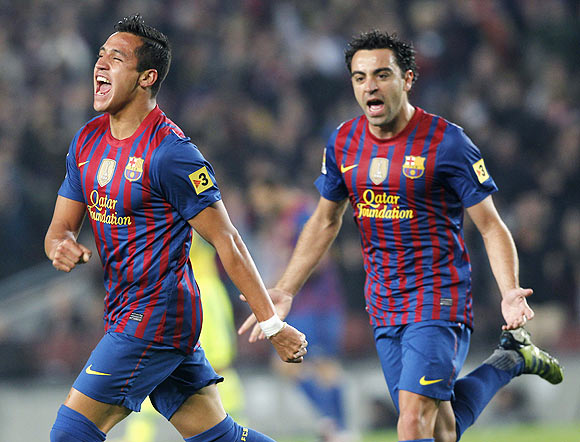 Barcelona's Alexis Sanchez (left) and Xavi Hernandez celebrate a goal against Getafe on Tuesday