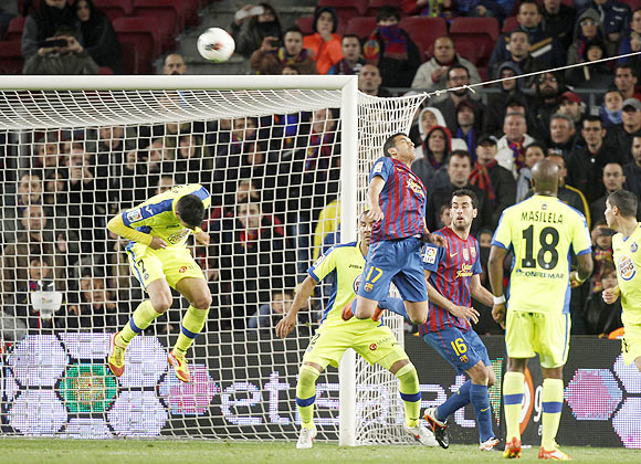 Barcelona's Pedro (17) heads the ball to score against Getafe
