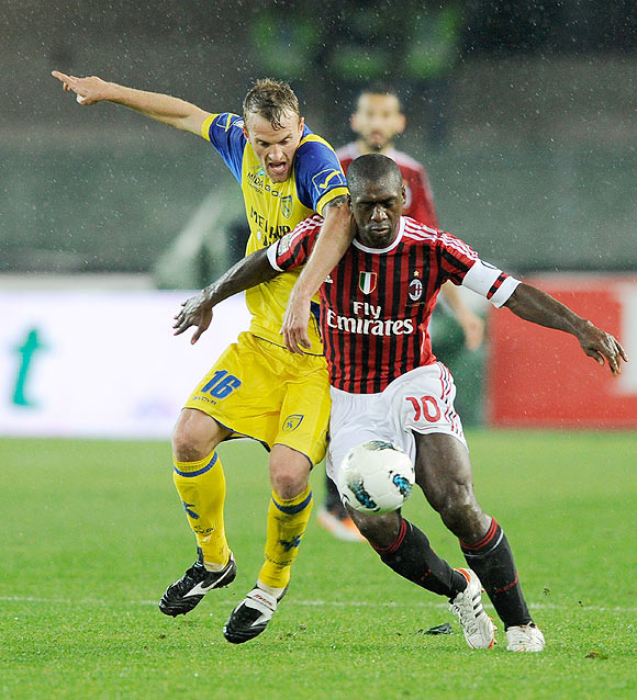 Clarence Seedorf of AC Milan (right) and Luca Rigoni Chievo Verona compete for the ball