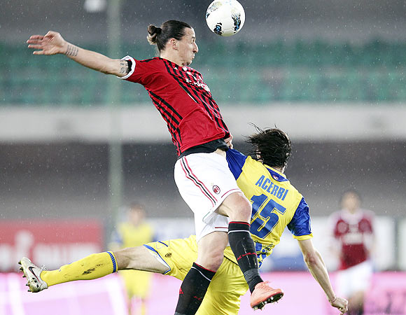 AC Milan's Zlatan Ibrahimovic (left) and Chievo Verona's Francesco Acerbi are involved in an aerial challenge