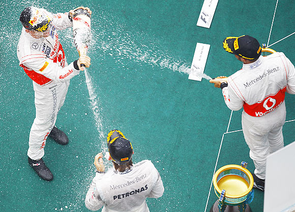 McLaren Formula One driver Jenson Button (left), team-mate Lewis Hamilton (right) and Mercedes Formula One driver Nico Rosberg spray champagne at each other