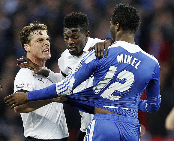 Tottenham Hotspur's Emmanuel Adebayor (centre) pushes teammate Scott Parker (left) away from Chelsea's John Obi Mikel (right) as they get into a bust-up during their FA Cup semi-final on Sunday