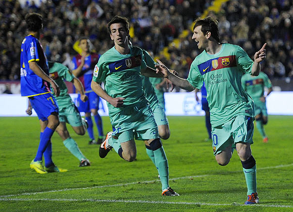 Barcelona's Lionel Messi (right) celebrates after scoring against Levante during their La Liga match on Saturday