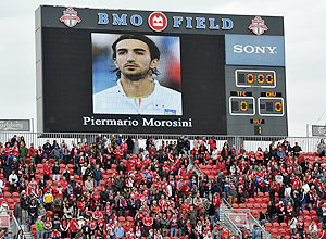 Toronto FC fans stand for a moment of silence in honour of Livorno's Piermario Morosini before the team's MLS soccer match against Chivas USA in Toronto on Sunday