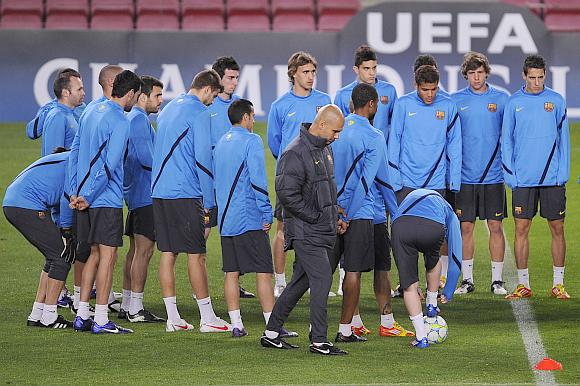 Head coach Josep Guardiola (right) of FC Barcelona walks pass his players during a training session