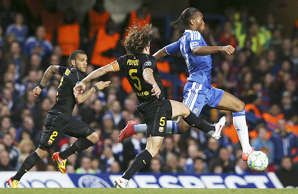 Carles Puyol (centre) of Barcelona and Didier Drogba (right) of Chelsea chase the ball during their Champions League match at Stamford Bridge