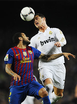 Dani Alves of FC Barcelona (left) duels for a high ball with Cristiano Ronaldo of Real Madrid