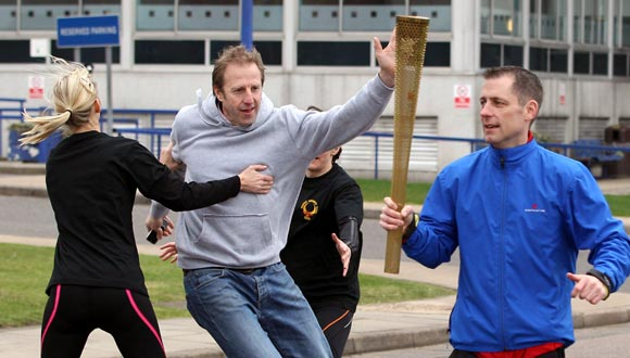Men stage an attack during a training session for the Olympic Torch Security Team who will be protecting the torch bearers and Olympic flame during the torch relay's progress through the UK, at the Metropolitan Police Training School in London.