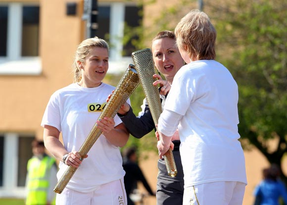 Runners practice a change over of the London 2012 Olympic Torch at a torch relay dress rehersal at Loughborough University