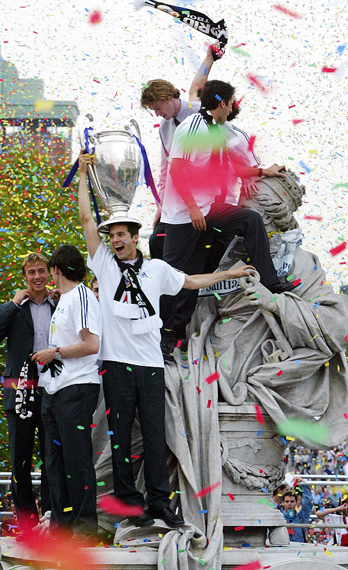 Real Madrid's Argentine player Santiago Solari holds the Champions League trophy as his teammates celebrate in central Madrid atop the landmark Cibeles fountain in the year 2002