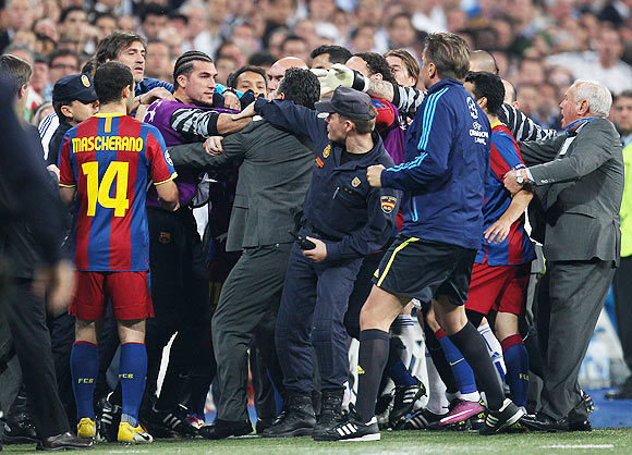Jose Pinto of Barcelona clashes with Real Madrid official as the players leave the pitch