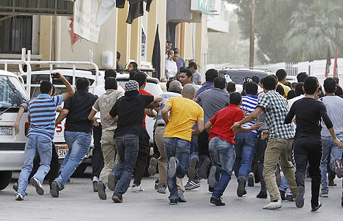 A protester shouts at riot police during an anti-government rally in Manama