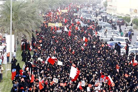 Protesters wave the Bahraini flags as they march on Budaiya highway during an anti-government protest by Bahrain's main opposition party Al Wefaq