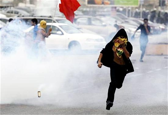 A protester runs away from tear gas released by riot police during clashes after the rally by Bahrain's main opposition party Al Wefaq in Budaiya, west of Manama