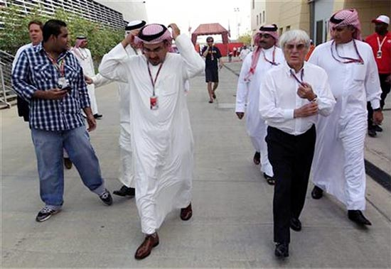 F1 supremo Bernie Ecclestone walks on the paddock with Crown Prince Sheikh Salman bin Hamad al-Khalifa and a government delegation after the second practice session of the Bahrain F1 Grand Prix at the Sakhir circuit in Manama