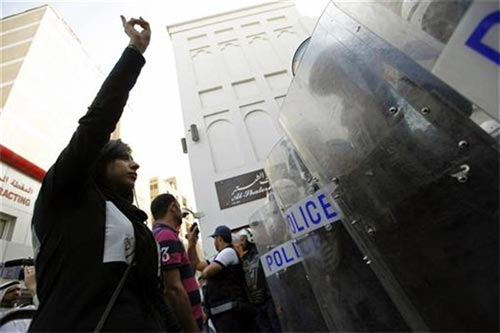 Zaynab (left), daughter of human rights activist Abdulhadi al-Khawaja, confronts riot police during an anti-government rally demanding his release, in Manama