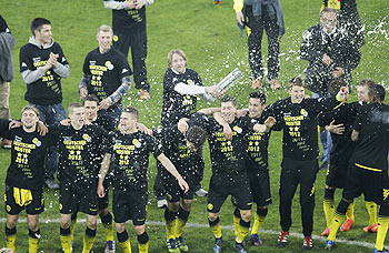 Players of Borussia Dortmund are soaked in beer as they celebrate after winning the Bundesliga championship following their win over Borussia Moenchengladbach in Dortmund on Saturday