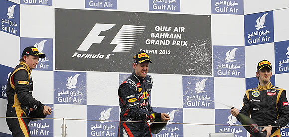 Red Bull's Sebastian Vettel (centre), Lotus driver Kimi Raikkonen and his teammate Romain Grosjean spray champagne on the podium after the Bahrain F1 Grand Prix